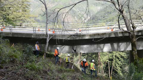 In this Wednesday, Feb. 22, 2017 photo, Caltrans engineers evaluate storm damage near a large crack where the Pfeiffer Canyon Bridge is sagging on Highway 1 in Big Sur, California. (David Royal /The Monterey County Herald via AP)
