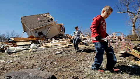 Kadin Lance, right, and his brother Carter Lance pick up debris at a friend's destroyed home Tuesday, March 7, 2017, after a tornado damaged tore through Oak Grove, Missouri, Monday night. (AP Photo/Charlie Riedel)