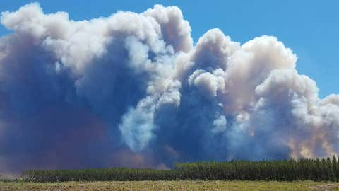 In this Saturday, May 6, 2017 photo provided by the Okefenokee National Wildlife Refuge, smoke rises from a wildfire east of Fargo, Georgia. (Ben Palm/Okefenokee National Wildlife Refuge via AP)