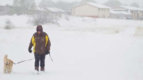 Betty Holmes walks her 6-year-old golden retriever, Snowy, through a field off of Spring Creek Drive in Laramie, Wyoming, during a snowstorm on Thursday, May 18, 2017. (Shannon Broderick/Laramie Daily Boomerang via AP)