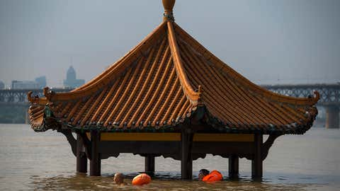 In this Monday, July 3, 2017 photo, people swim past a pagoda in a flooded riverside park in Wuhan in central China's Hubei Province. Dozens of people have been killed and more are missing as heavy rains continue to pummel southern China, flooding towns, cutting off power and halting traffic, China's Ministry of Civil Affairs said Tuesday. (Chinatopix Via AP)