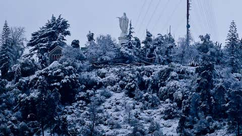 A statue of the Blessed Virgin Mary stands on the summit of the snow-covered San Cristobal Hill, in Santiago, Chile, on July 15, 2017. (AP Photo/Esteban Felix)