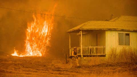 Flames rise behind a vacant house as a firefighter works to halt the Detwiler wildfire near Mariposa, California, on Wednesday, July 19, 2017. (AP Photo/Noah Berger)