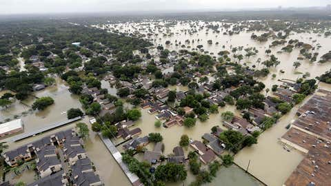 In this aerial photo, a neighborhood near Addicks Reservoir are flooded by rain from Tropical Storm Harvey Tuesday, Aug. 29, 2017, in Houston. (AP Photo/David J. Phillip)