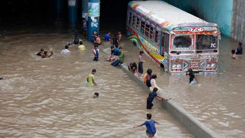 Pakistani children play in an underpass filled with rainwater in Karachi, Pakistan, Thursday, Aug. 31, 2017. Torrential monsoon rains are lashing Pakistan's port city of Karachi following days-long downpours in neighboring India that especially caused havoc in Mumbai. (AP Photo/Fareed Khan)