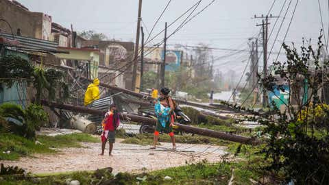Residentes caminan cerca de líneas de energía caídas debido al Huracán Irma en Caibarién, Cuba, el sábado 9 de septiembre de 2017. No se informaron muertes ni lesiones después de que la lluvia y los vientos fuertes de Irma azotaran el noreste de Cuba. El mar aumentó tres cuadras tierra adentro en el Caribe. (Fotografía de AP/Desmond Boylan)