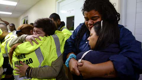 Rescue team members Candida Lozada, left, and Stephanie Rivera, second from left, Mary Rodriguez, second from right, and Zuly Ruiz, right, embrace as they wait to assist in the aftermath of Hurricane Maria in Humacao, Puerto Rico, Wednesday, Sept. 20, 2017. (AP Photo/Carlos Giusti)