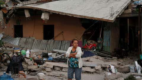 A woman stands outside a partially collapsed home after an 7.1 earthquake, in Jojutla, Morelos state, Mexico, Wednesday, Sept. 20, 2017. Police, firefighters and ordinary Mexicans are digging frantically through the rubble of collapsed schools, homes and apartment buildings, looking for survivors of Mexico's deadliest earthquake in decades as the number of confirmed fatalities climbs. (AP Photo/Eduardo Verdugo)