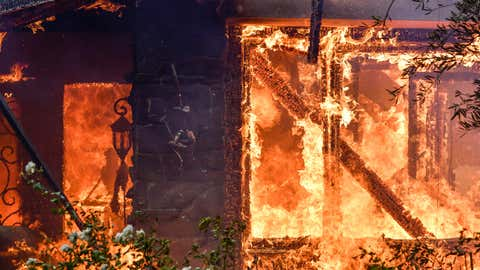 Flames from a wildfire consume a home in Anaheim Hills, California, on Oct. 9, 2017. (Jeff Gritchen/The Orange County Register via AP)