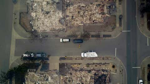 In this aerial image people look at homes that were destroyed by a wildfire in Santa Rosa, Calif., Tuesday, Oct. 10, 2017. Newly homeless residents of California wine country took stock of their shattered lives Tuesday, a day after deadly wildfires destroyed homes and businesses. (Nick Giblin/DroneBase via AP)