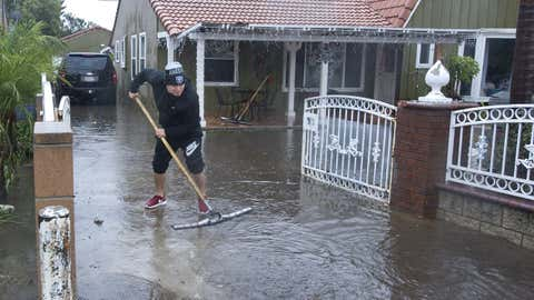 A resident of one of the houses on E. McFadden Avenue in Santa Ana, Calif., squeegees water out of the driveway of the home, Wednesday, Jan. 6, 2016.  El Nino storms lined up in the Pacific, promising to drench parts of the West for more than two weeks and increasing fears of mudslides and flash floods in regions stripped bare by wildfires. At least two more storms are expected to follow bringing as much as 3 inches of rain. (Sam Gangwer/The Orange County Register via AP)