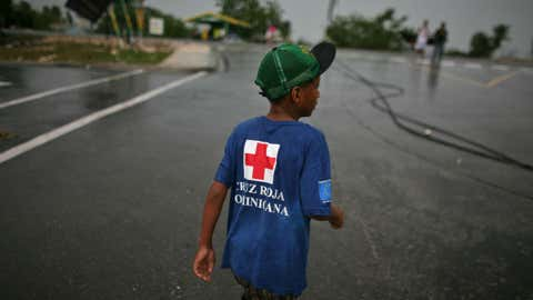 Wearing a Dominican Red Cross t-shirt a kid walk in the street after Tropical Storm Isaac hit in Barahona, Dominican Republic, Saturday, Aug. 25, 2012.