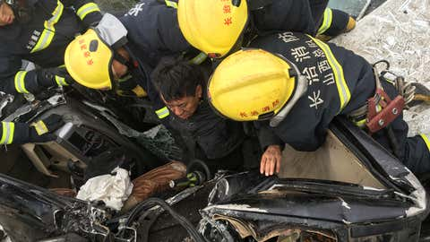 Firefighters try to rescue people trapped in a car pileup on a section of Taiyuan-Changzhi Expressway in Taiyuan city, north China's Shanxi province, Dec. 8, 2015. (AP Photo/Sun Jiang)