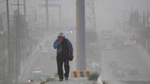 A man uses his shirt to cover his face as he walks through the ash-covered streets of San Andres Cholla, Mexico, Monday April 18, 2016, after the Popocatepetl volcano erupted overnight, spewing ash on nearby towns. Officials there are urging to people to wear masks to avoid inhaling the fine grit that has covered houses and cars. (AP/Pablo Spencer)