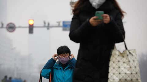A woman wears a protection mask as she walks along a street on a polluted day in Beijing, Tuesday, Dec. 8, 2015. Schools closed and rush-hour roads were much quieter than normal as Beijing's first-ever red alert for smog took effect Tuesday, closing many factories and invoking restrictions to keep half the city's vehicles off the roads. (AP Photo/Andy Wong)