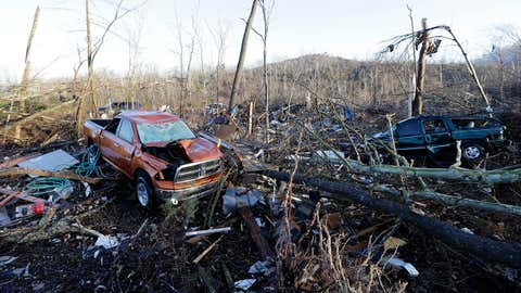 Vehicles and debris are scattered in an area near Linden, Tenn., Thursday, Dec. 24, 2015. Several people were killed in Mississippi, Tennessee and Arkansas as spring-like storms mixed with unseasonably warm weather spawned rare Christmastime tornadoes in the South. (AP Photo/Mark Humphrey)