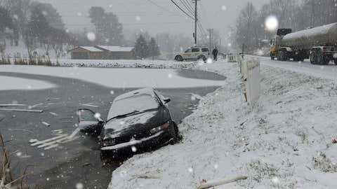 A driver lost control of her car and crashed through a fence and into a pond an Walnut Hill Road in Sullivan County near Bristol, Tenn., Wednesday, Jan. 2, 2016. during an afternoon snowfall.  The driver was able to get out the passenger side and walk to a local business to call the Sheriff's Deptartment for help. (Earl Neikirk/The Bristol Herald-Courier via AP)