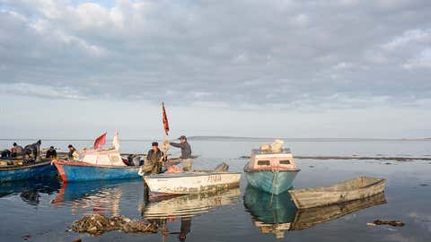 At 10 a.m., near the village of Tastubek, fishermen prepare materials for the day's fishing. Recent strong winds kept fishermen from making a large catch over the past few days, but this morning the sun is shining. Snow, ice and rain rarely stop the fishermen, but wind is their enemy. (Didier Bizet)