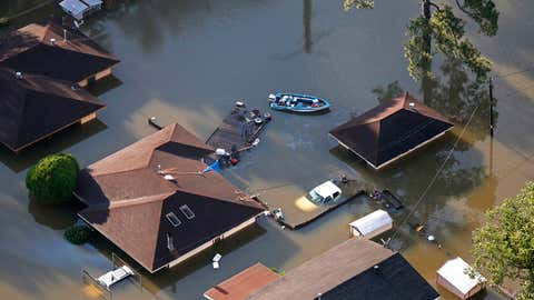 A boat sits near flooded homes in the aftermath of Tropical Storm Harvey in Beaumont, Texas, Thursday, Aug. 31, 2017. (AP Photo/Gerald Herbert)