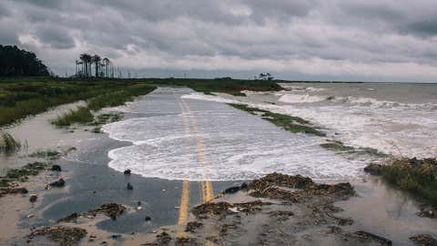 Water spills onto Hoopers Island Road, up the coast from Crisfield, Maryland, during high tide. The bay is a foot deeper than it was at the start of the 20th century, meaning that storm surges are higher and land in the region is sinking. (© 2013 Greg Kahn)