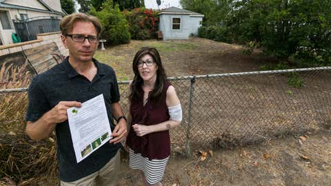 Michael Korte and his wife Laura Whitney, pose outside their home lawn in Glendora, Calif., Thursday, July 17, 2014. (AP Photo/Damian Dovarganes)