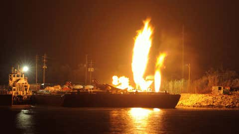 Fire burns aboard two fuel barges along the Mobile River after explosions sent three workers to the hospital Wednesday April 24, 2013. (AP Photo/John David Mercer)