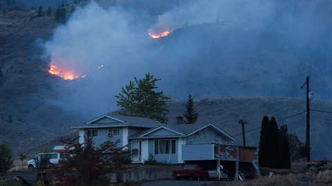 A wildfire burns on a mountain in the distance behind a house that remains standing on the Ashcroft First Nation, near Ashcroft, B.C., late Sunday July 9, 2017. As if the risk of losing their homes isn't enough, wildfire evacuees in British Columbia have faced the additional threat of looters searching through their belongings after they rushed to safety. THE CANADIAN PRESS/Darryl Dyck via 660News.com
