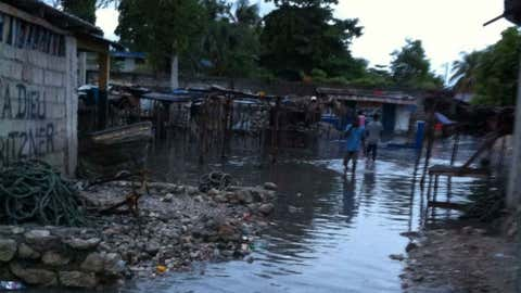 Residents wading through water in Belle Anse, Haiti, on Monday.