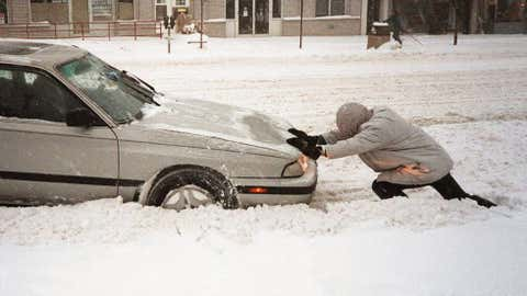 An unidentified man pushes a car out of the snow January 7, 1996 in Washington, D.C. Image credit: BOB PEARSON/AFP/Getty Images
