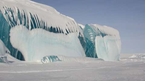 Though they appear to be frozen ocean waves, these blue ice towers in Antarctica are created when ice compresses, forcing trapped air bubbles out. When sunlight passes through this thick frozen ice, blue light waves are visible but the red light is absorbed. (Photo credit: Tony Travouillon)
