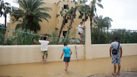 Tourist Cesar Calzada, center, of Mexico City, climbs over a fence of the Riu resort to get out of the hotel and go search for food after Hurricane Odile severely damaged the hotel in Los Cabos, Mexico, Monday, Sept. 15, 2014. (AP Photo/Victor R. Caivano)