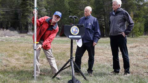Frank Gehrke, left, chief of the California Cooperative Snow Surveys Program for the Department of Water Resources, points to a mark on the snow pack measuring pole that was the lowest previous snow pack level as Gov. Jerry Brown, center and Mark Cowin, director of the Department of Water Resources look on at a news conference near Echo Summit, Calif., Wednesday, April 1, 2015.