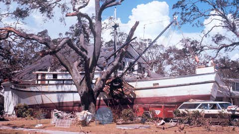 One of only three Category 5 U.S. landfalls, Camille devastated the Mississippi Gulf Coast. At the time of its landfall on the night of Aug. 17-18, 1969, the minimum surface pressure was 900 millibars. The exact wind speeds in Camille will never be known, as all wind-measuring instruments near the core of the storm were destroyed. The storm surge of 24 feet in southern Mississippi set a U.S. record that would later be surpassed by Hurricane Katrina. Because Camille was compact, the devastating surge focused on a narrower swath of coastline than that of Katrina. More than 140 people died as a result of Camille's landfall, and another 113 perished in Virginia from flash flooding resulting from the storm's remnants. (Photo: A ship carried by Camille's storm surge rests alongside a home in Biloxi, Mississippi; NOAA Photo Library)
