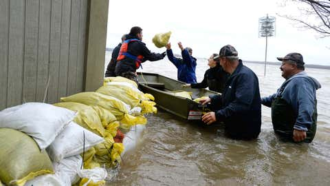 Volunteers put sandbags around a home on Voisine Road in Rockland, Ont., about 40 kilometres east of Ottawa, Sunday, May 7, 2017, as rising levels on the Ottawa River and heavy rains continue to cause flooding. (Justin Tang/The Canadian Press via AP)