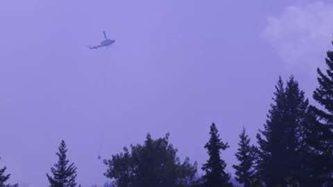 A helicopter flies above smoky skies in Canim Lake, B.C. Courtesy of Canim Lake General Store, via Facebook.