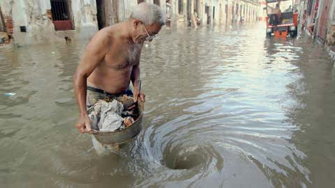 A man carrying a bucket full of trash comes closer to a whirlpool formed by the water flooding through the street sewage 24 October, 2005 in Havana, Cuba, after the devastating passage of Hurricane Wilma. (ADALBERTO ROQUE/AFP/Getty Images)