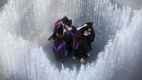 Graduates celebrate after leaving their graduation ceremony at the Royal Festival Hall by entering the fountain 'Appearing Rooms', by Danish artist Jeppe Hein, on the Southbank in high temperatures on July 18, 2013 in London, England. (Oli Scarff/Getty Images)