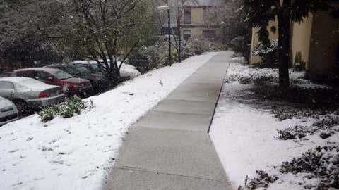 Snow falls on a sidewalk in Philadelphia, Pennsylvania, on April 9, 2016.