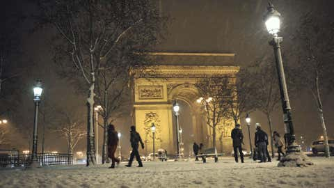 People walk in the snow-covered Champs-Elysees in Paris after the snow fell over the French capital this week. (Mehdi Fedouach/AFP/Getty Images)