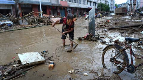 In this Sunday, July, 10, 2016 photo released by Xinhua News Agency, a woman clears mud and debris on a street following Typhoon Nepartak hit in Minqing county in southeast China's Fujian province. Several people dead and missing after Typhoon Nepartak battered China's coastal Fujian Province with heavy rain and strong winds that toppled homes and triggered landslides, government agencies said. (Zhang Guojun/Xinhua via AP)