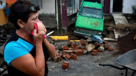 Maria del Carmen Gonzalez watches after part of a street and her home collapsed due to heavy rains in the Gulf port city of Veracruz, Mexico, Tuesday Sept. 2, 2014. (AP Photo/Felix Marquez)