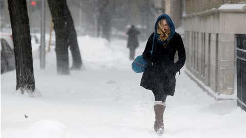 A commuter walks against blowing snow Wednesday, Feb. 5, 2014, in Chicago. Heavy, blowing snow is moving across much of Illinois as the state gets pelted by the latest round of winter weather. (AP Photo/Kiichiro Sato)