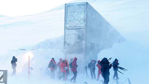 Journalists and cameramen walk under a gust of cold wind near the entrance of the Svalbard Global Seed Vault, officially opened near Longyearbyen, Norway, on Feb. 26, 2008. (Larsen, Hakon Mosvold/AFP/Getty Images)