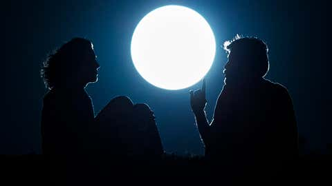 A couple talk as they sit against  the perigee moon, also known as a supermoon, in Madrid, Sunday, Aug. 10, 2014. (AP Photo/Andres Kudacki)