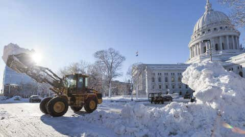 Crews remove piled-up snow from around the Capitol Square, December 21, 2012. A day after Draco hit Wisconsin, schools were closed.