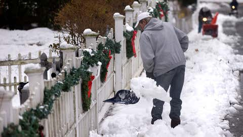 Steve Roche shovels snow as neighbors use snow blowers to clear the sidewalk, Dec. 15, 2013, in Walpole, Mass. (AP Photo/Steven Senne)