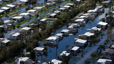FILE - In this Sept. 16, 2017, file photo, this aerial photo shows flooded homes of Citrus Park in Bonita Springs, Fla., six days after Hurricane Irma. The same technology that connected students and teachers in the aftermath of hurricanes Harvey and Irma is easing their transition back to class. That technology includes smartphone exchanges, social media, messaging apps and websites. (Nicole Raucheisen/Naples Daily News via AP, File)