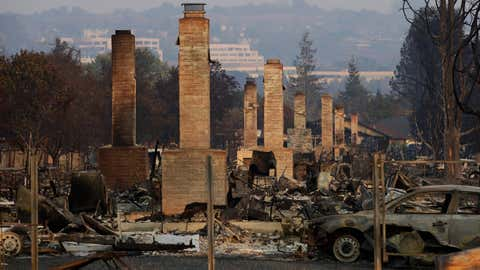 A row of chimneys stand in a neighbourhood devastated by a wildfire Friday, Oct. 13, 2017, near Santa Rosa, Calif. Firefighters gained some ground on a blaze burning in the heart of California's wine country but face another tough day ahead with low humidity and high winds expected to return. (AP Photo/Jae C. Hong)