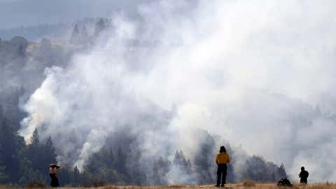 A firefighter, center, and two onlookers watch a smoldering wildfire from a hilltop, Sunday, Oct. 15, 2017, in Oakville, Calif. With the winds dying down, fire officials in California say they are finally getting the upper hand against the wildfires that have devastated wine country and other parts of the state over the past week. (AP Photo/Marcio Jose Sanchez)