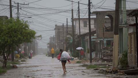 Residents walk in rain brought on by Hurricane Irma, in Caribbean, Cuba, Friday, Sept. 8, 2017. Irma battered Cuba on Saturday with deafening winds and unremitting rain, pushing seawater inland and flooding homes before taking aim at Florida. Early Saturday, the hurricane center said the storm was centered about 10 miles (15 kilometers) northwest of the town of Caibarien. (AP Photo/Desmond Boylan)